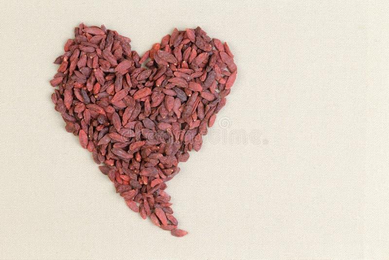 La forme de coeur a formé des baies sèches saines de goji image stock