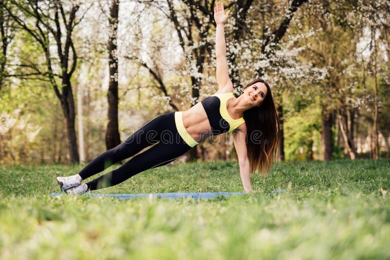 La forme physique, concept de mode de vie de sport faisant le yoga s'exerce sur des tapis dehors image libre de droits
