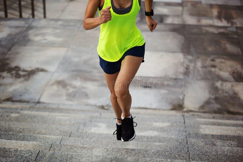La forme physique folâtre la femme courant sur des escaliers de ville photo libre de droits
