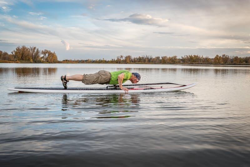 La forme physique tiennent dessus le paddleboard photos libres de droits