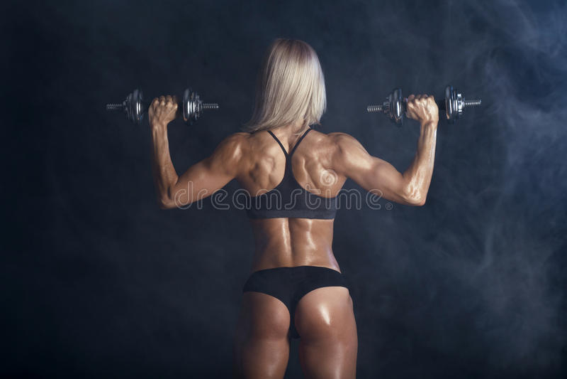 La forte donna sexy sta preparandosi con i bilancieri fotografia stock