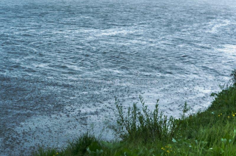 La forte pluie frappe l'eau, temps inclément avec la pluie photo libre de droits