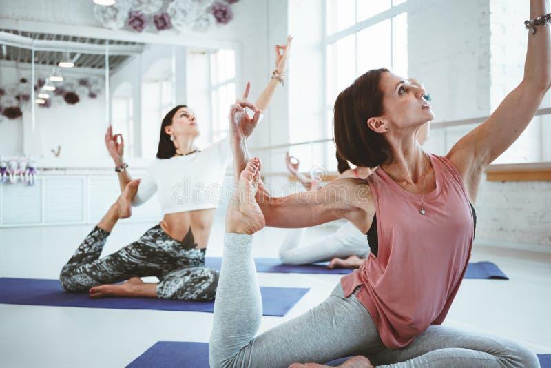 La forte yoga adatta di addestramento della donna posa sulla stuoia di forma fisica insieme al gruppo di persone su fondo Cura e  fotografie stock