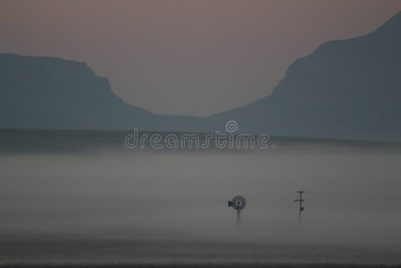 La foschia di primo mattino sopra agricoltori sistema con i mulini a vento ed i raccolti a mala pena visibili fotografie stock libere da diritti