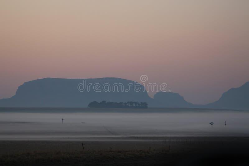 La foschia di primo mattino sopra agricoltori sistema con i mulini a vento ed i raccolti a mala pena visibili fotografie stock