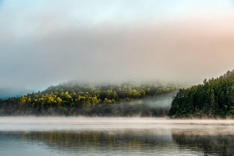 La foschia di primo mattino toglie un piccolo, lago riflettente fotografie stock libere da diritti