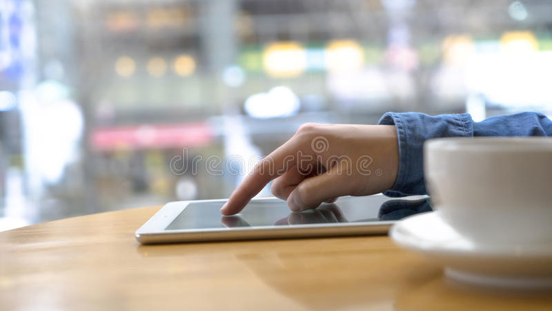La foto ascendente cercana de la tableta con el hombre da el tiro macro el usar en el café y el té de consumición Fla borroso de  fotos de archivo