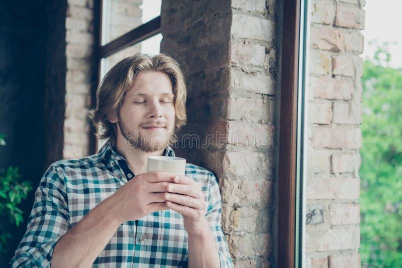 La foto ascendente cercana de la taza preciosa de la tenencia del hombre que olía con sus ojos cerró la camisa de tela escocesa a fotos de archivo libres de regalías