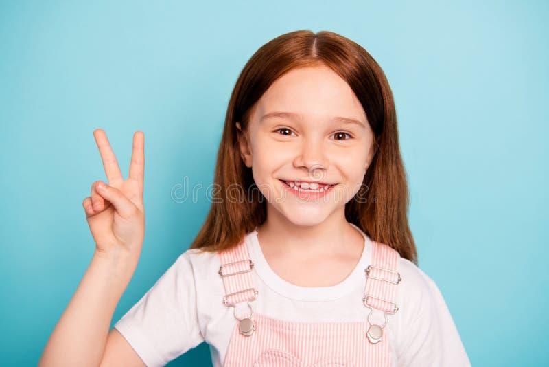 La foto ascendente cercana del niño encantador hace las v-muestras el fondo azul aislado contento fotografía de archivo libre de regalías