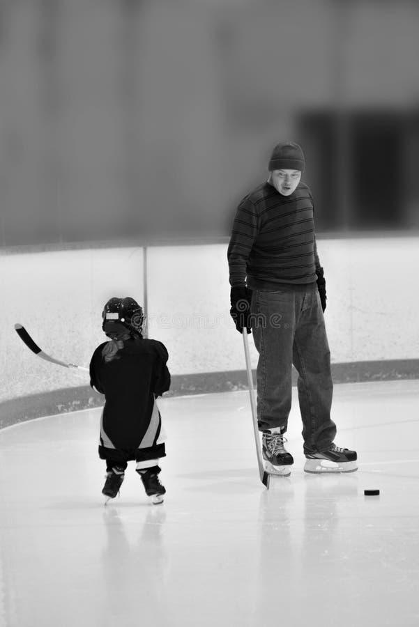 La foto bianca del nero e del whiteBlack e di poca ragazza dell'hockey sta durando in attrezzatura piena: il casco, emette luce,  fotografia stock