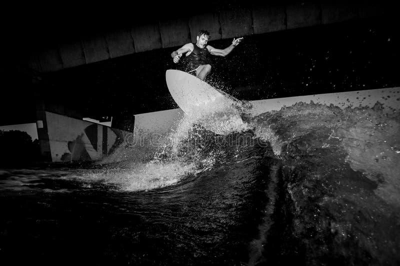 La foto blanco y negro del montar a caballo activo del wakesurfer en el río agita fotos de archivo libres de regalías