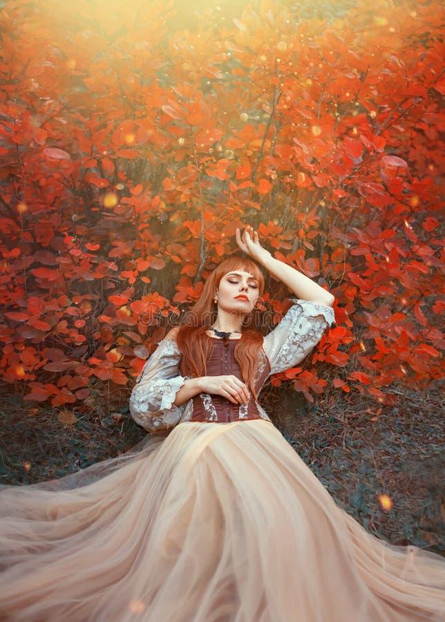 La foto caliente de la bella durmiente, muchacha del arte con el pelo rojo ardiente miente en la tierra en bosque denso debajo de fotografía de archivo