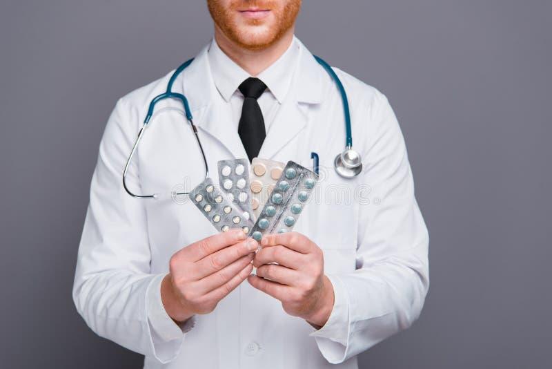 La foto cosechada de las manos del doc. lleva a cabo paquetes de las píldoras aislados en gra oscuro fotografía de archivo