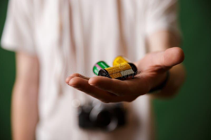La foto cosechada de la mano masculina, sosteniendo la cámara rueda, focu selectivo imagen de archivo libre de regalías