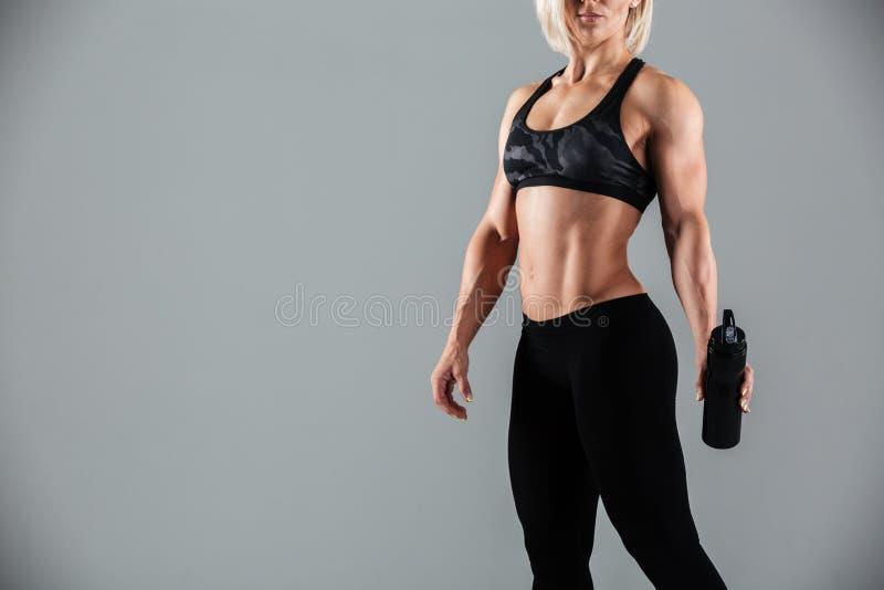 La foto cosechada del blonde fuerte se divierte a la mujer que sostiene la botella de wa imagen de archivo