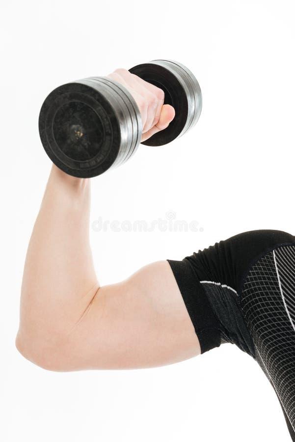 La foto cosechada del deportista fuerte hace ejercicios de los deportes con pesa de gimnasia imagen de archivo
