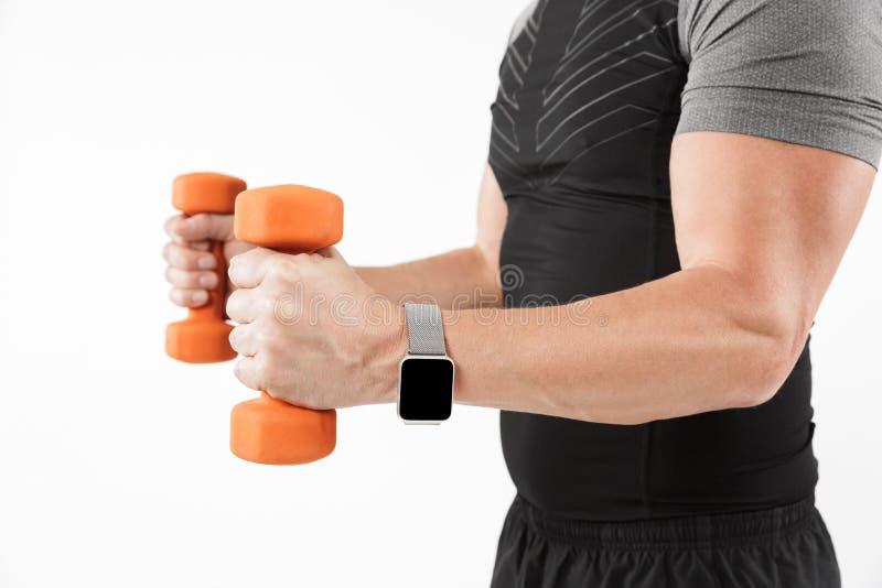 La foto cosechada del deportista maduro fuerte hace ejercicios con pesas de gimnasia fotografía de archivo
