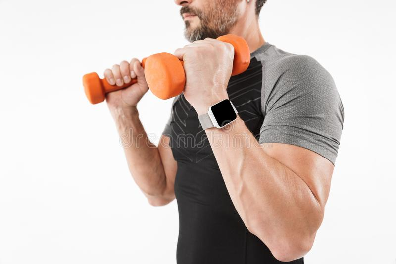 La foto cosechada del deportista maduro fuerte hace ejercicios con pesas de gimnasia fotografía de archivo libre de regalías