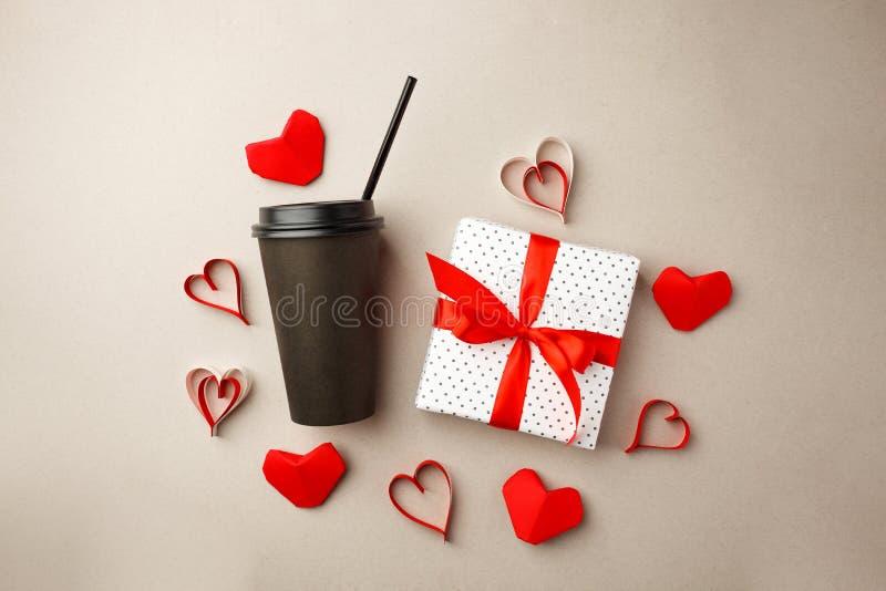 La foto creativa del concepto de elegante negro se lleva la taza de café con la cinta roja de la caja de regalo y el marco de cor imagenes de archivo