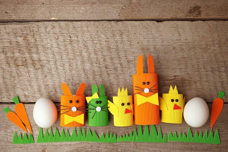 La foto creativa linda con los huevos de Pascua, el cratf de papel diy chiken y el conejito de pascua, concepto de la primavera d imagenes de archivo