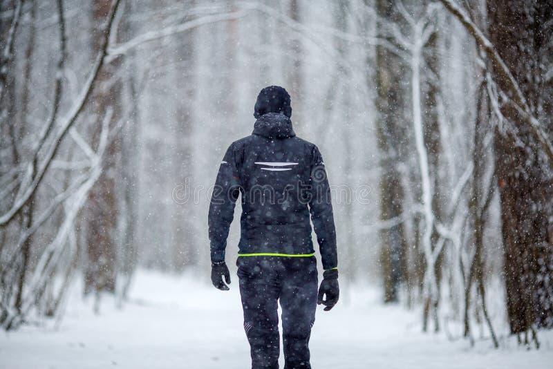 La foto dalla parte posteriore dell'uomo negli sport copre sul funzionamento dell'inverno fotografie stock