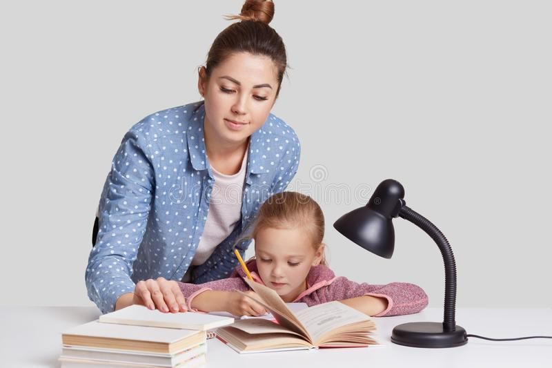 La foto de la actitud de la madre y del daugher en la mesa junta, información del wrtite en cuaderno, leyó muchos libros, se prep imagen de archivo libre de regalías