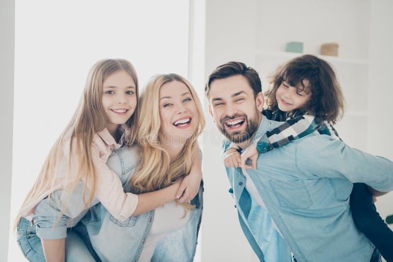 La foto de cuatro miembros que el abrazo de la familia lleva a pequeños niños lleva a cuestas los apartamentos de la posición den imagenes de archivo