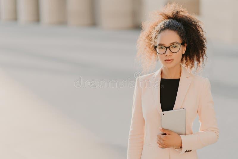 La foto de la empresaria afroamericana elegante utiliza la tableta al aire libre, lleva la chaqueta blanca formal, vidrios transp imágenes de archivo libres de regalías