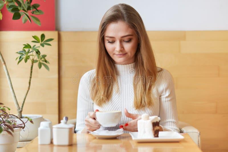 La foto de la hembra cabelluda ligera relajada bebe el café caliente o el cappucino con el postre delicioso, se sienta en cafeter imagen de archivo libre de regalías