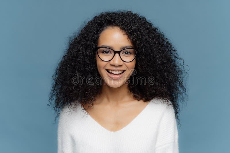 La foto de la hembra pelada oscura alegre con el pelo quebradizo espeso, sonríe feliz en la cámara, disfruta el día agradable, ve foto de archivo libre de regalías