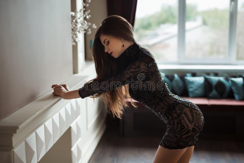 La foto de la moda de la señora hermosa se vistió en la igualación del vestido negro del cordón Mujer joven que presenta de maner imagenes de archivo