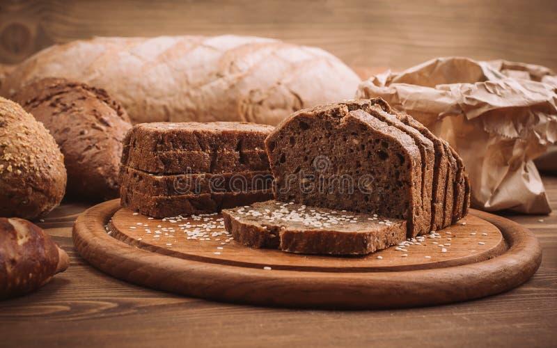 La foto de muchos mezcló los panes cocidos en la tabla de madera rústica fotos de archivo