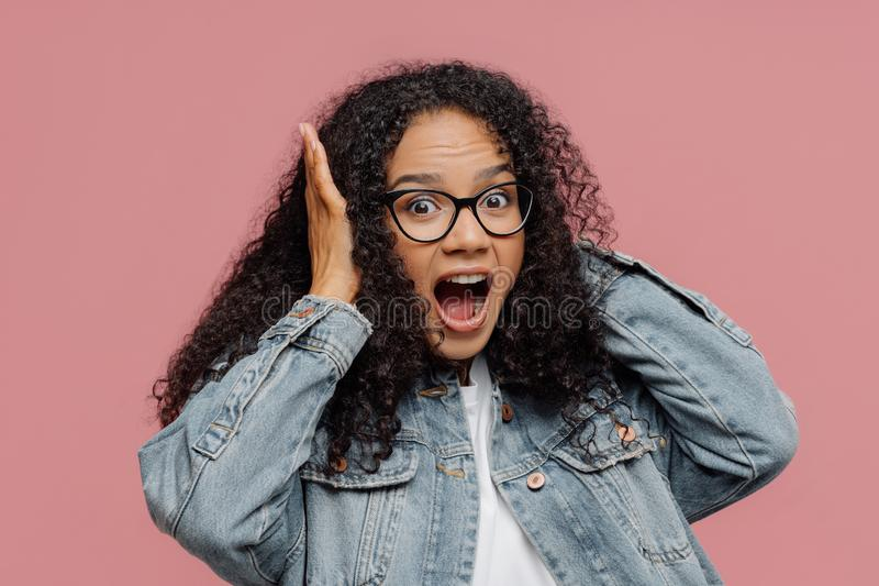 La foto de la mujer afroamericana sorprendida cubre los oídos, grita en alta voz, ignora el sonido ruidoso, guarda la boca abrió, foto de archivo