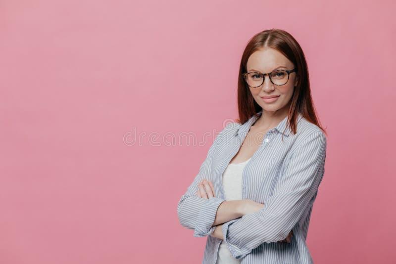 La foto de la mujer atractiva con la expresión segura de sí mismo, mantiene los brazos doblados, lleva gafas y la camisa rayada,  fotos de archivo libres de regalías