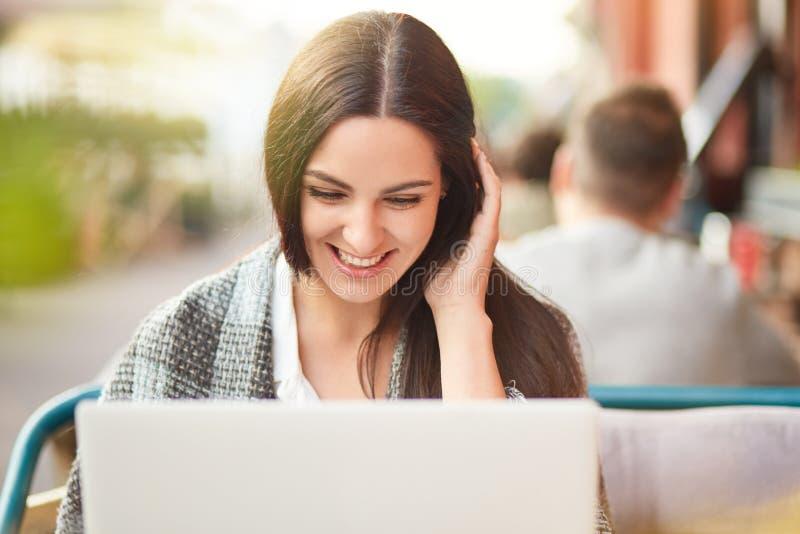 La foto de la mujer caucásica satisfecha alegre mira positivamente la pantalla del ordenador portátil, tiene sobrecama, sigue ley imagen de archivo libre de regalías