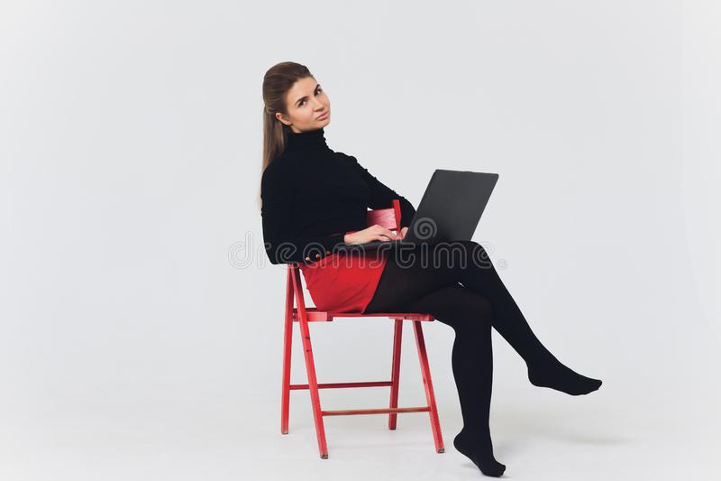 La foto de la mujer hermosa 20s que sonreía y que usaba el ordenador con las piernas cruzó aislado sobre el fondo blanco imagen de archivo