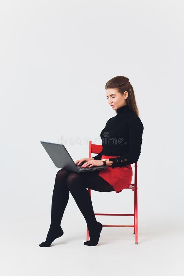 La foto de la mujer hermosa 20s que sonreía y que usaba el ordenador con las piernas cruzó aislado sobre el fondo blanco foto de archivo libre de regalías