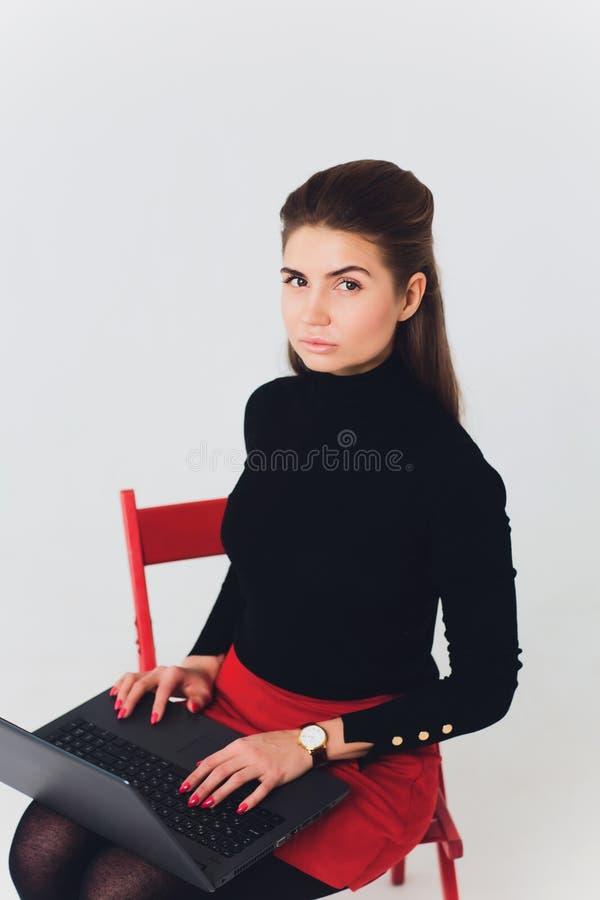 La foto de la mujer hermosa 20s que sonreía y que usaba el ordenador con las piernas cruzó aislado sobre el fondo blanco foto de archivo