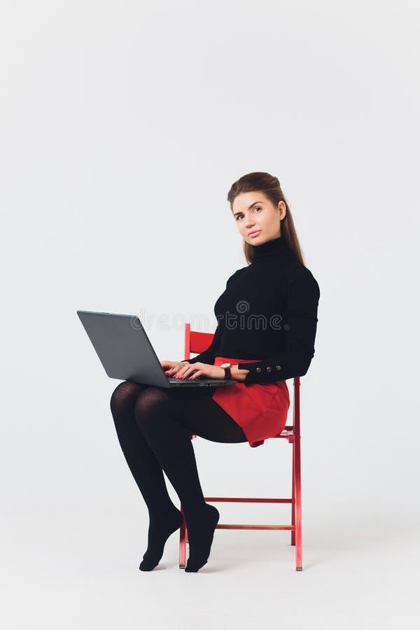 La foto de la mujer hermosa 20s que sonreía y que usaba el ordenador con las piernas cruzó aislado sobre el fondo blanco imágenes de archivo libres de regalías