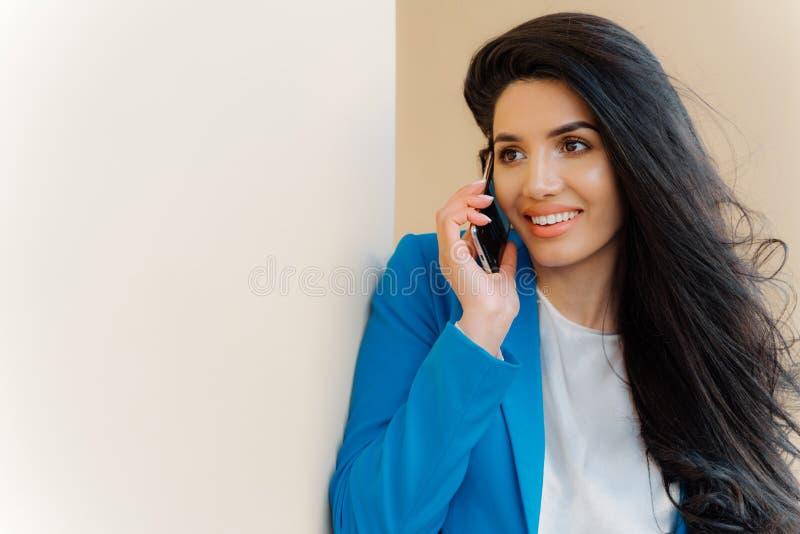 La foto de la mujer morena con aspecto agradable, pelo lujoso, negociaciones sobre el teléfono móvil, vestido en ropa formal, arr foto de archivo libre de regalías