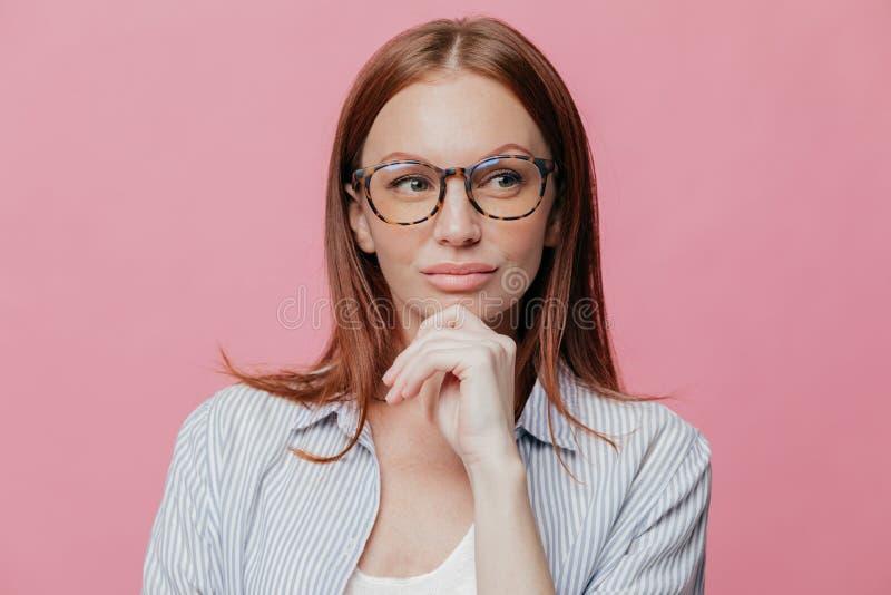 La foto de la mujer pensativa tiene expresión seria, guarda la mano en la barbilla, lleva los vidrios y la camisa elegante, aisla imagen de archivo libre de regalías