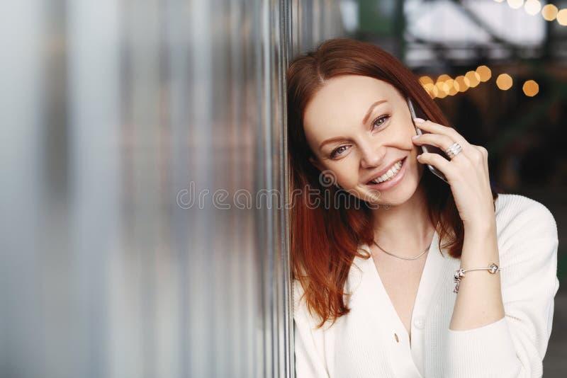 La foto de la mujer preciosa con el pelo rojizo, sonrisa positiva, tiene charla con el cliente, llamadas del teléfono al amigo, v imagenes de archivo