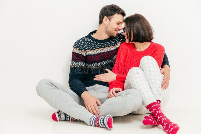 La foto de pares románticos en amor se sienta en el piso blanco cruzó las piernas imagenes de archivo