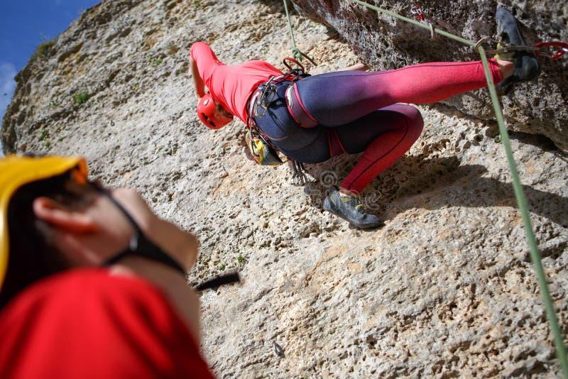La foto de la parte posterior de jóvenes se divierte a la mujer en el casco rojo que sube para arriba la montaña y a hombres con  fotos de archivo libres de regalías