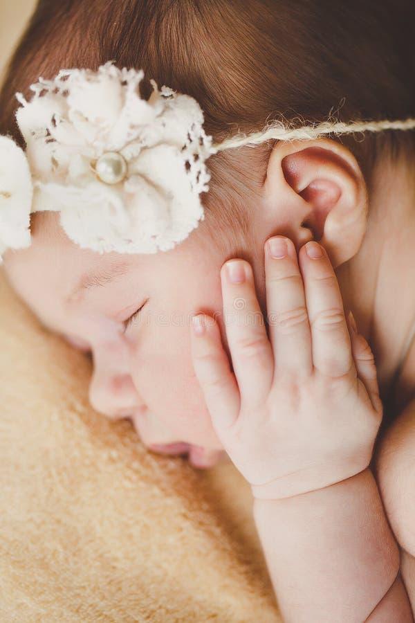 La foto de un bebé recién nacido encrespó para arriba dormir en una manta fotos de archivo
