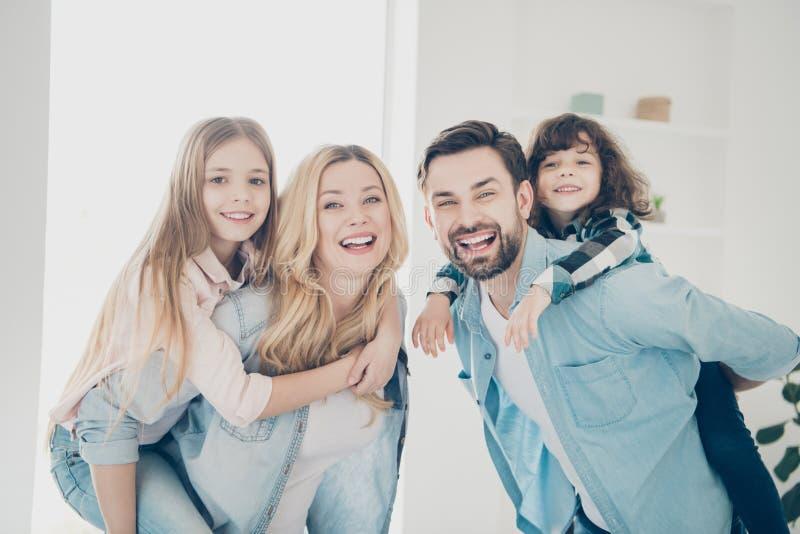 La foto del abrazo grande de los miembros de la familia cuatro lleva a pequeños niños para llevar a cuestas dentro los apartament foto de archivo libre de regalías