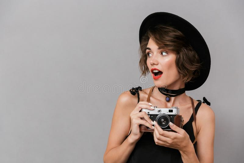 La foto del camerawoman 20s che indossa la tenuta nera del cappello e del vestito macera immagine stock