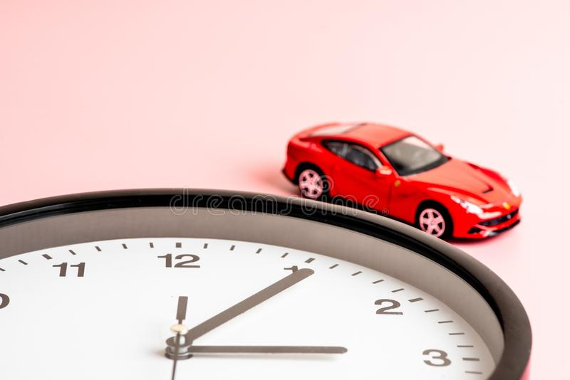 La foto del despertador y del coche hermosos formó el juguete en el préstamo rosado maravilloso del estudio imágenes de archivo libres de regalías