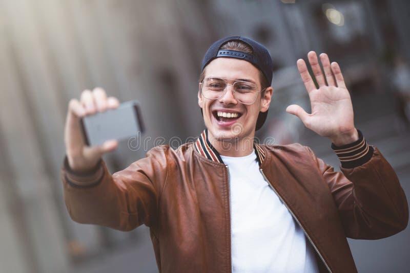 La foto del hombre caucásico joven feliz hermoso hace el selfie por la cámara en la calle fotografía de archivo libre de regalías