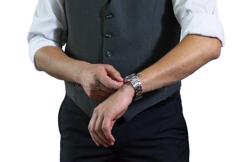 La foto del hombre de negocios en una camisa blanca y un chaleco gris el hombre abrocha horas imagenes de archivo